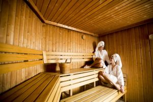 Two women in wellness and  spa center relaxing in wooden sauna